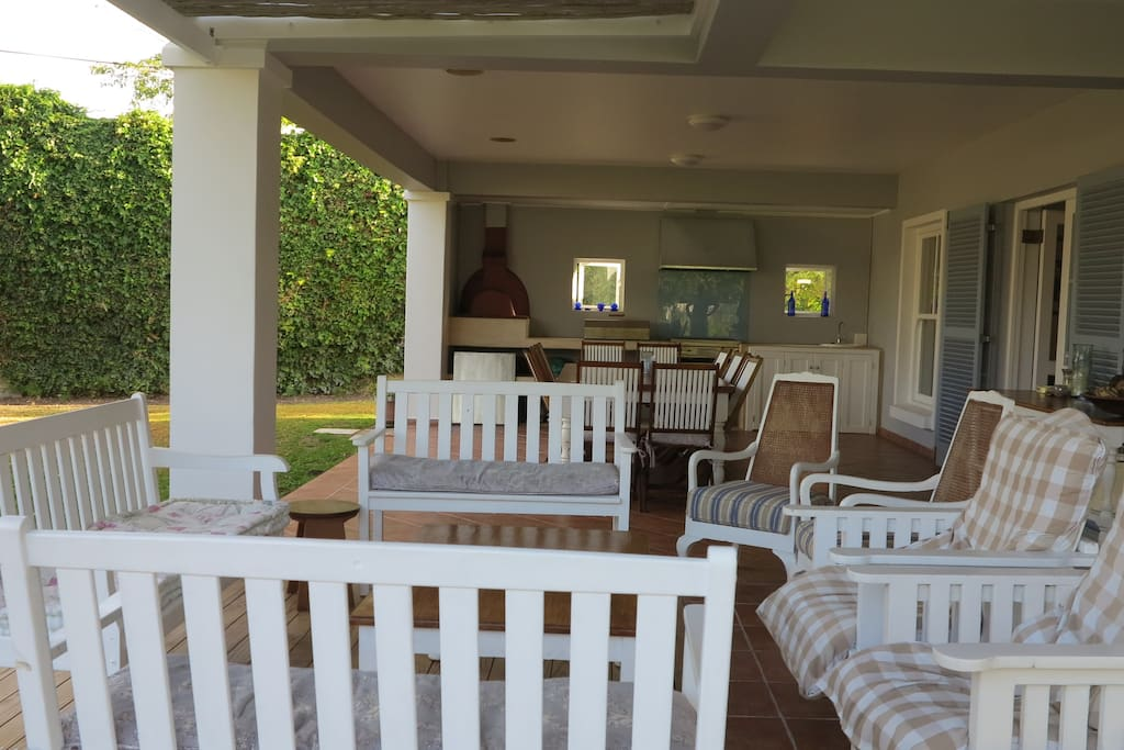 An outside covered patio. seating on benches and couches as well as  a 12 seater table. Gas barbeque