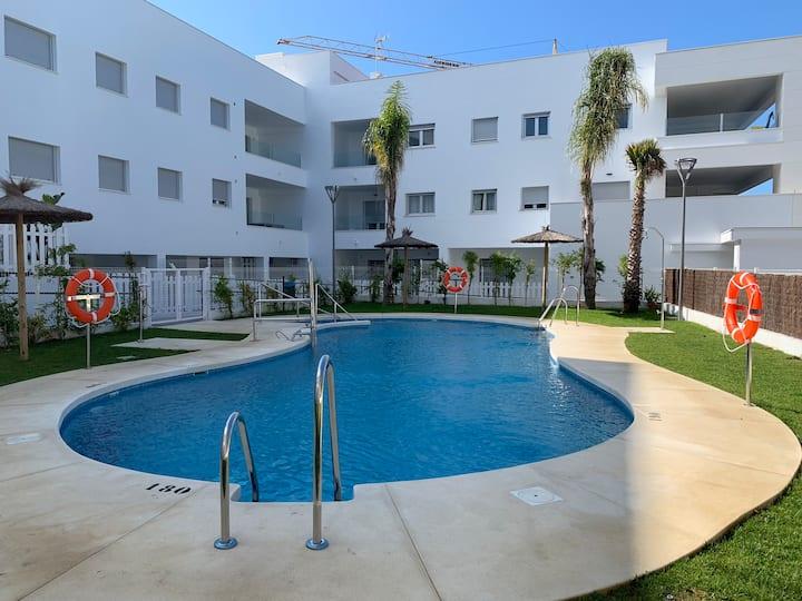 Apartamento con piscina y garaje junto a la playa.