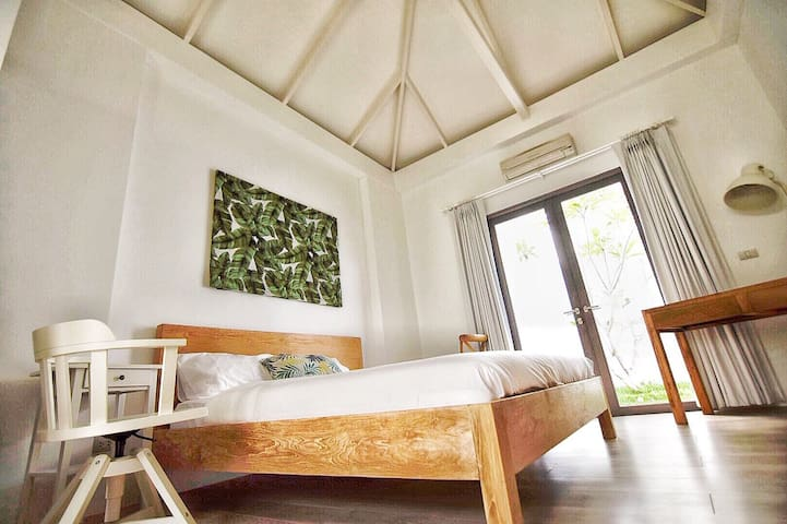 Balinese Teak King Bed and Tropical Art with a private garden courtyard.