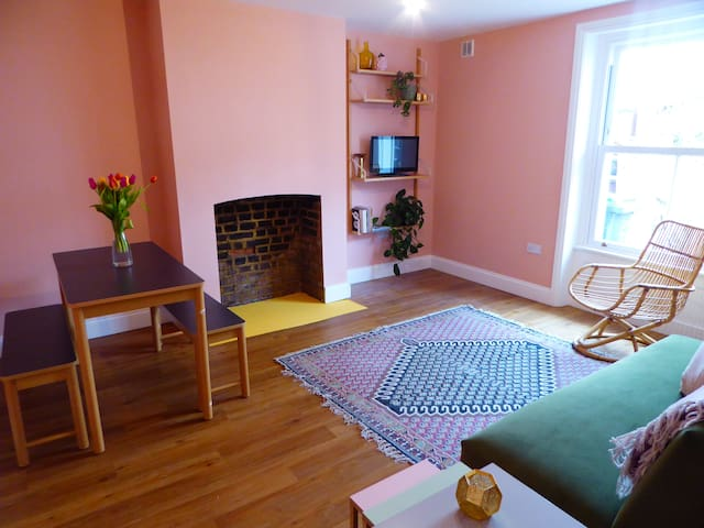 Bright a cosy living room with TV, books and dining table.