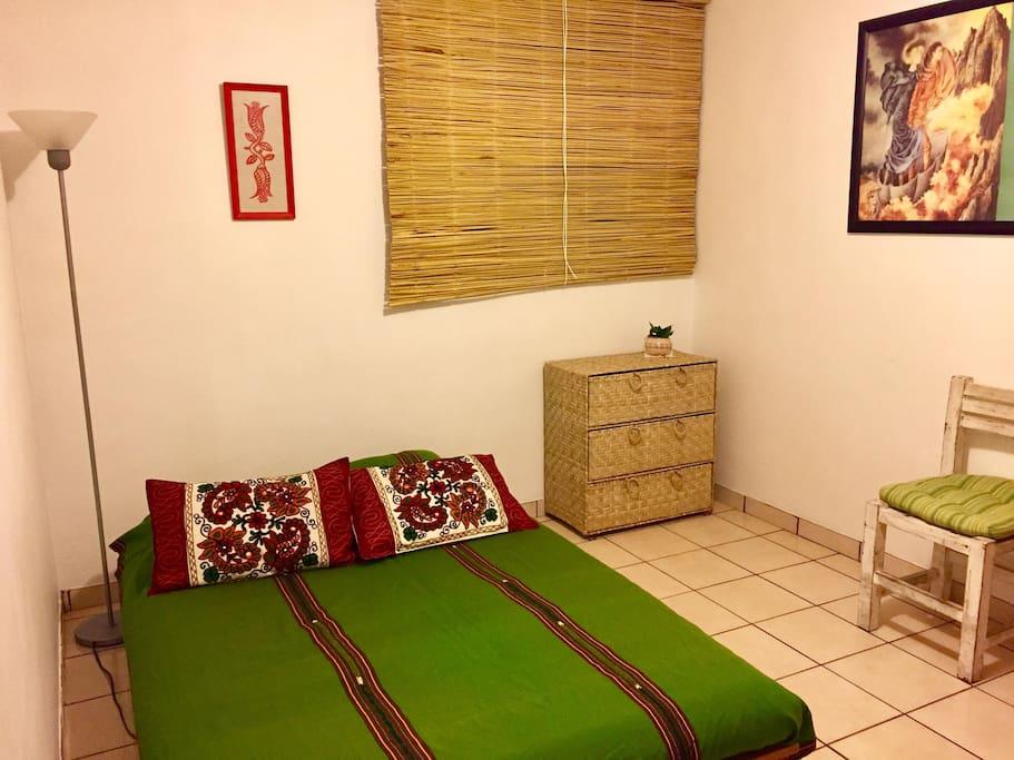 Otra toma de la habitación privada, de noche, la luz es cálida y el espacio acogedor y silencioso.