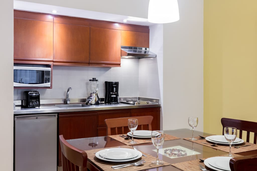 The kitchen features a stovetop, mini-fridge, microwave, coffeemaker, and blender.