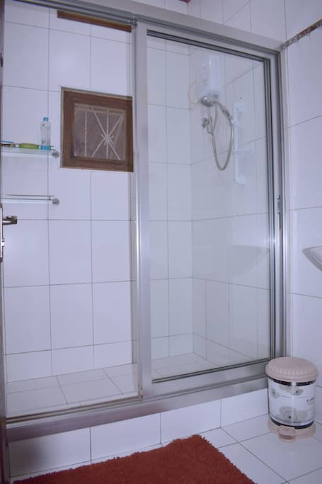 This is the shower room. Sparkling tidy with rugs for you to step after taking a shower.