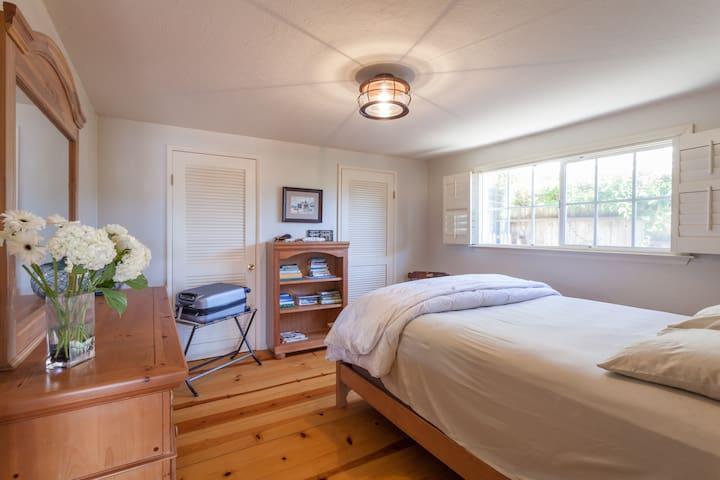 East bedroom.  Cal King Bed, Pine flooring, wood shutters