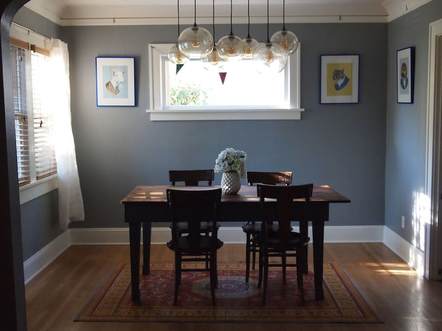Dining room with local Portland animal art, reclaimed barn wood table, and hand-carved 1910 seats for 4 (less unique IKEA folding chairs for 2 more).