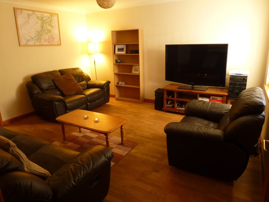 Comfortable lounge with Large TV, DVD player and leather reclining sofas.