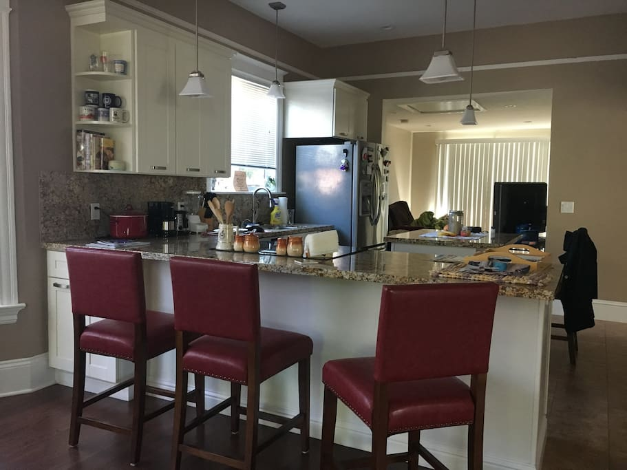 Newly remodeled open-concept kitchen with central island, dishwasher, microwave, and stainless steel refrigerator