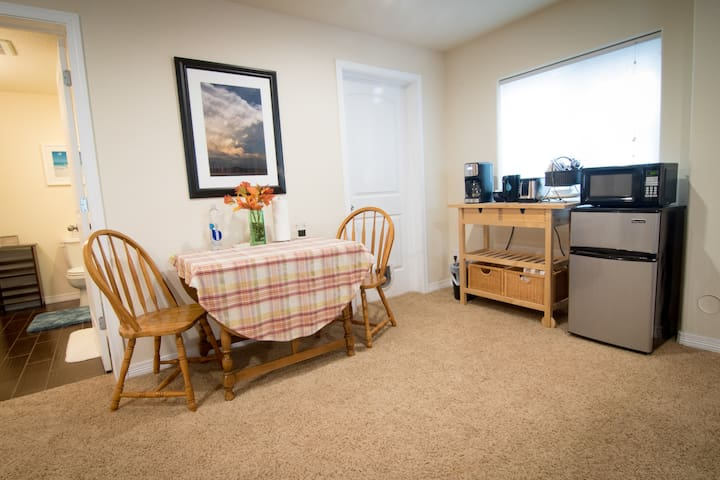 Kitchenette area with table, chairs, mini-fridge, microwave, coffeemaker, toaster, and dishes