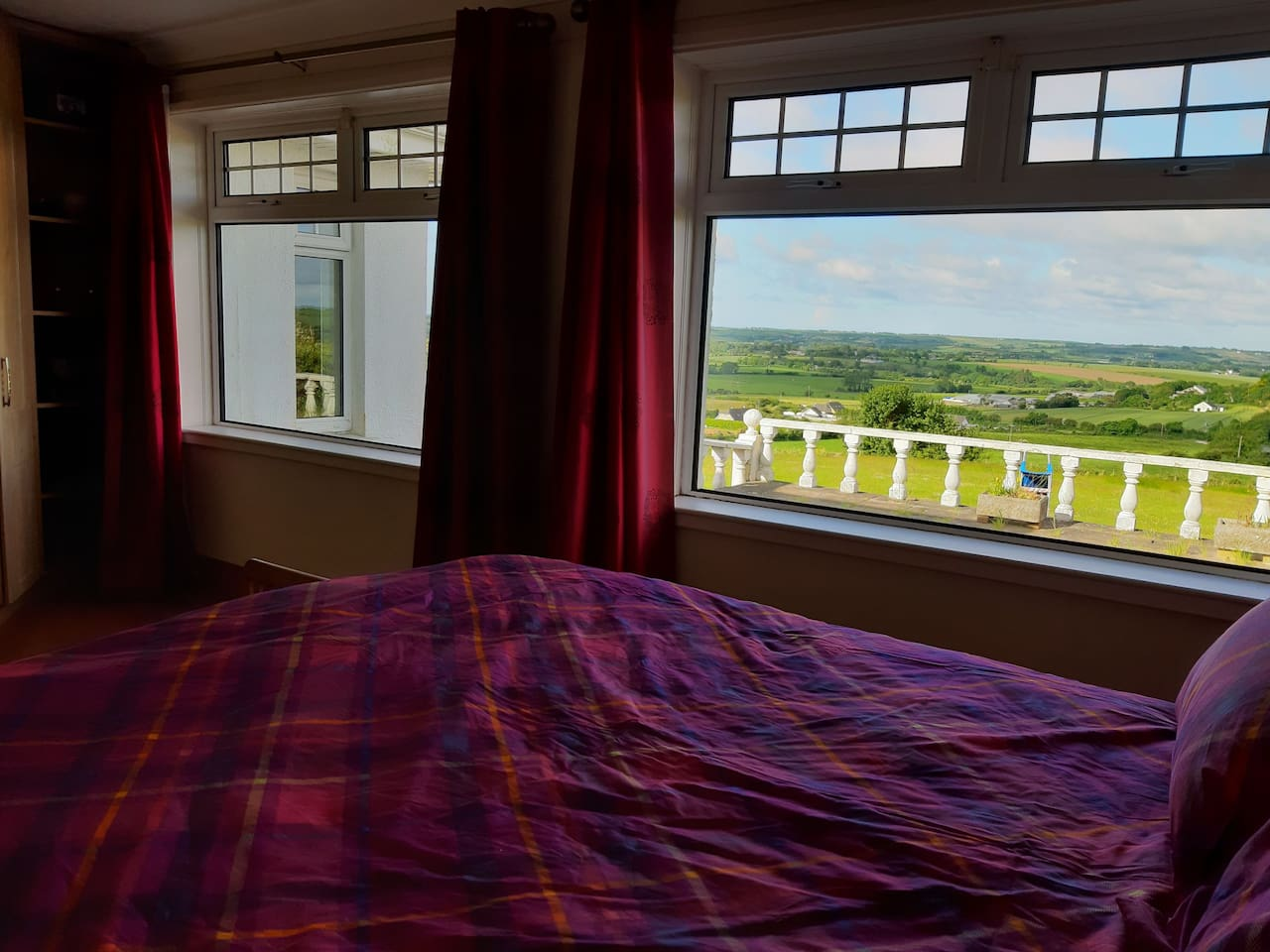 From the bright bedroom you'll see the surrounding valley of farm land and even glimpse the sea.