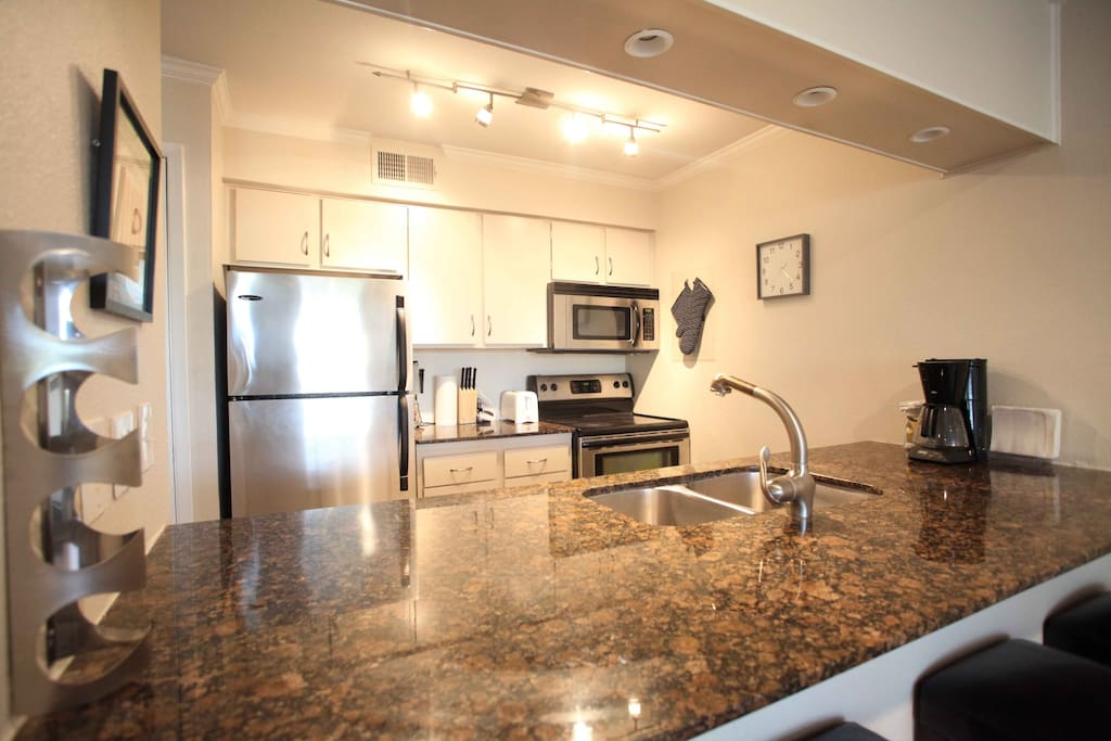 Full kitchen with granite counter top and stainless fridge