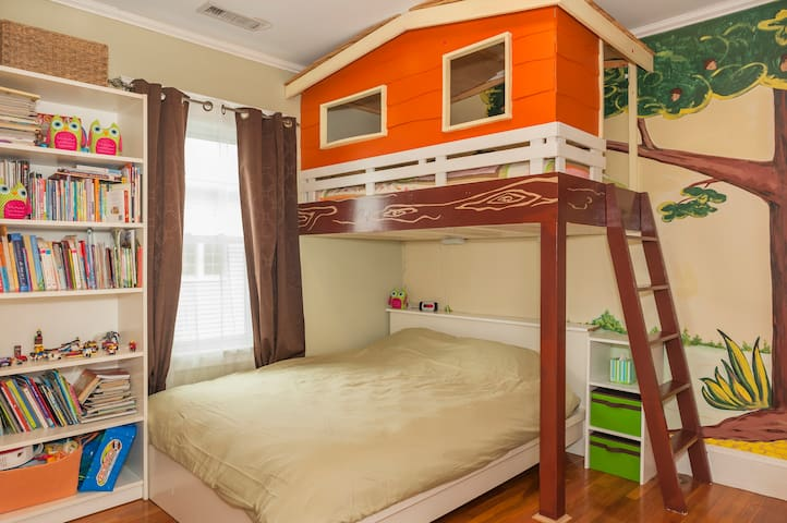 Custom built tree house bedroom with queen and twin sized bed.