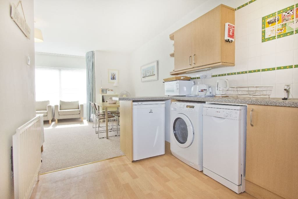 The kitchen is close to the dining area and has a washing machine with dryer, dishwasher and fridge