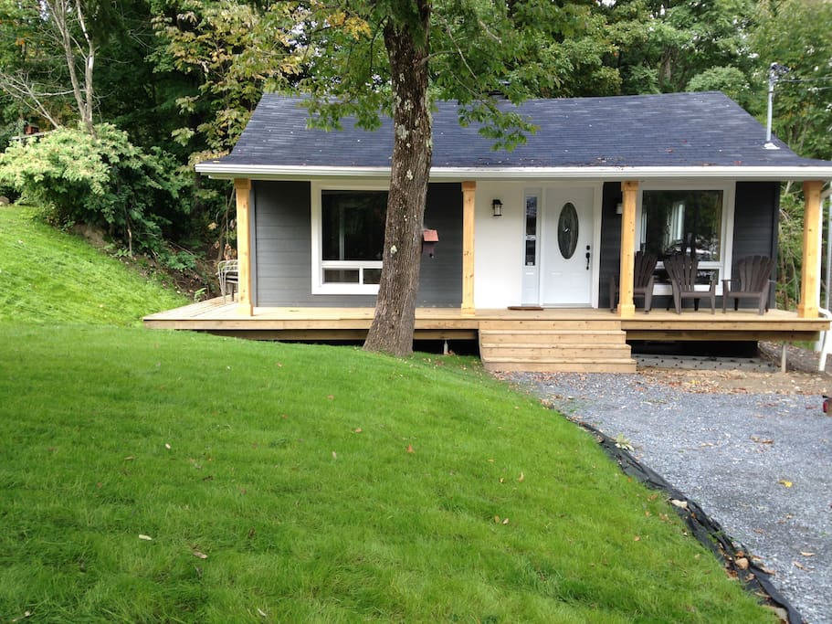 Chalet private front yard, large wrap around porch with parking for 4 cars.