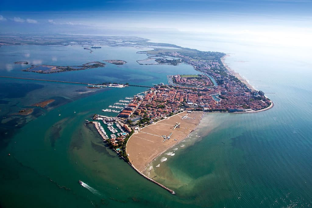 Aerial view of Grado showing lagoon, yacht mooring, city and beach
