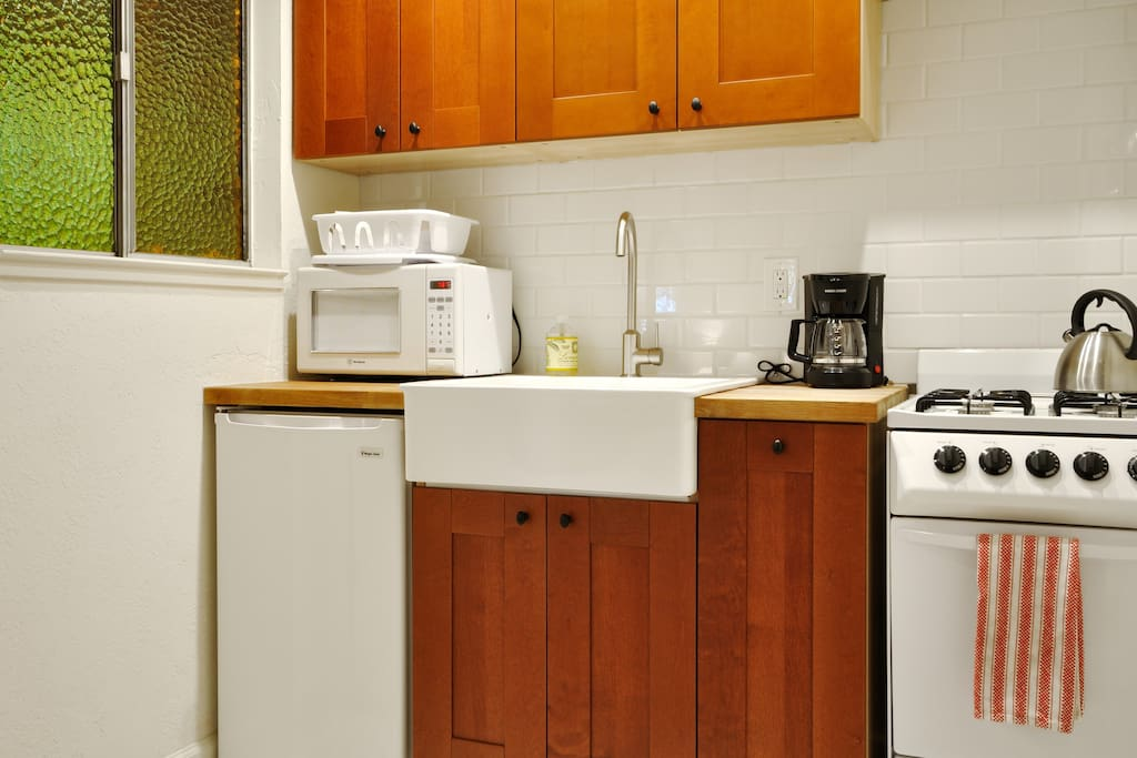 Kitchenette has farmhouse sink, apartment-size stove and refrigerator and a microwave and coffee maker