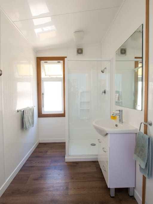Clean modern bathroom shared between only 2 rooms.