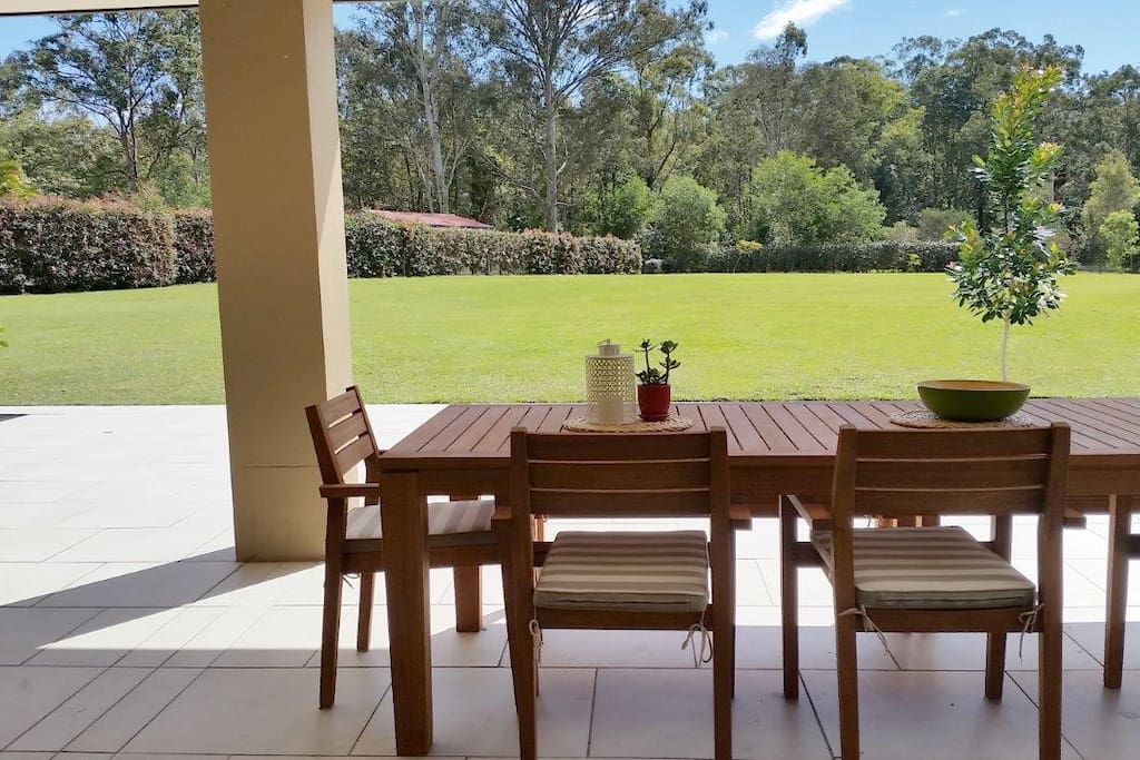 10 person outdoor dining table on the patio overlooking private level lawn and gardens