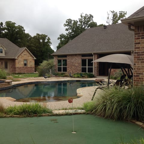 The putting green, pool and game room in front of the guest house.