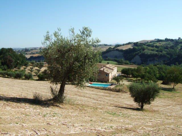 Casa Giulia below its pool, and surrounding view