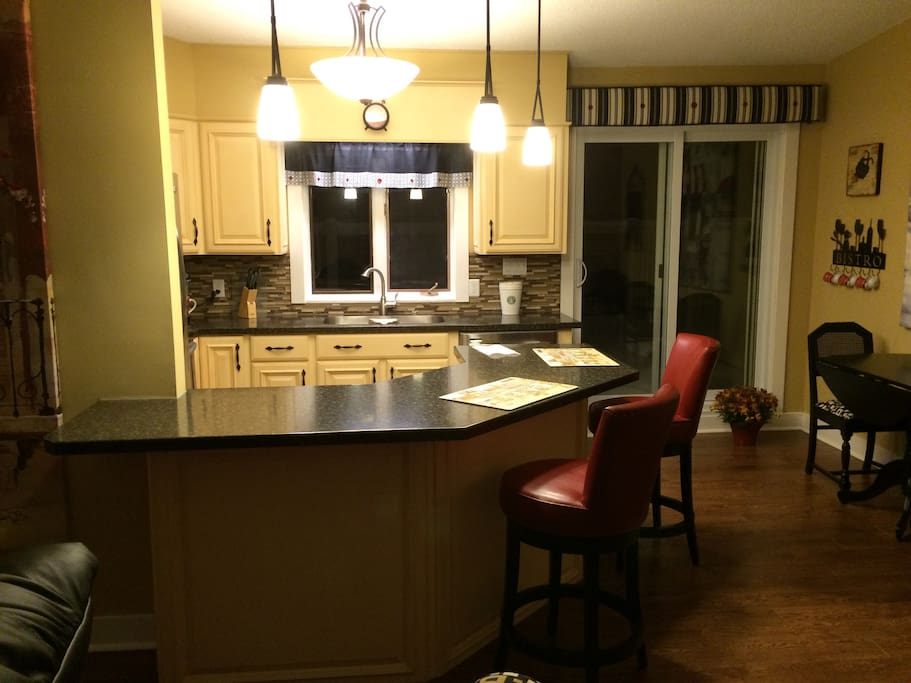 kitchen island with 2 red leather swivel counter stools