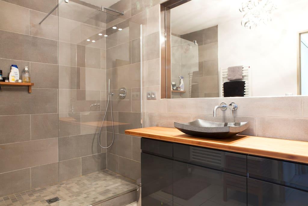 magnifique salle de bain avec grand miroir et douche italienne spacieuse.