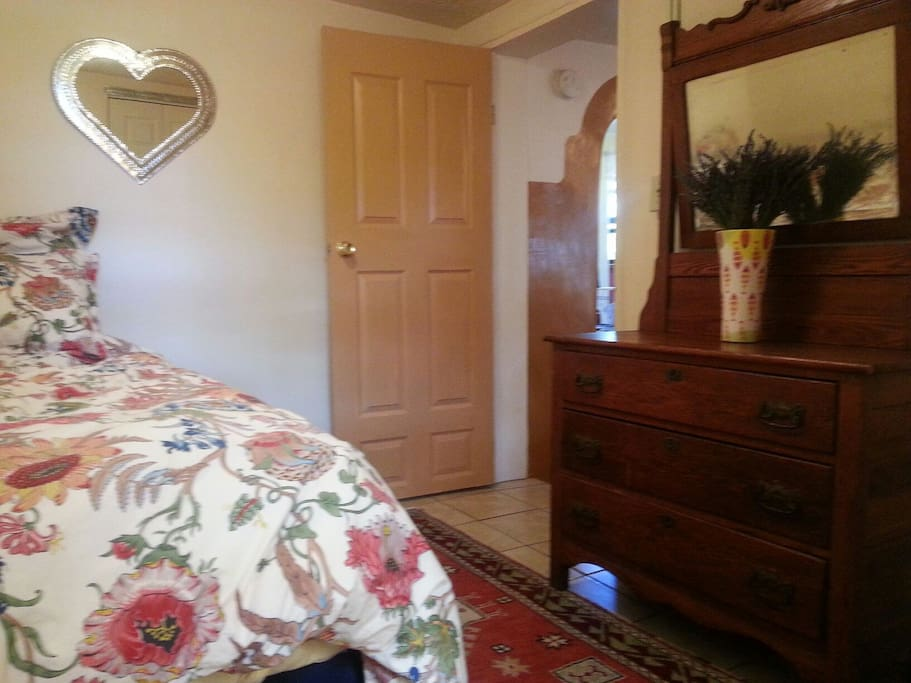 New bed and bedding in guest room, antiques and lovely rug. Closet with plenty of space for your belongings.