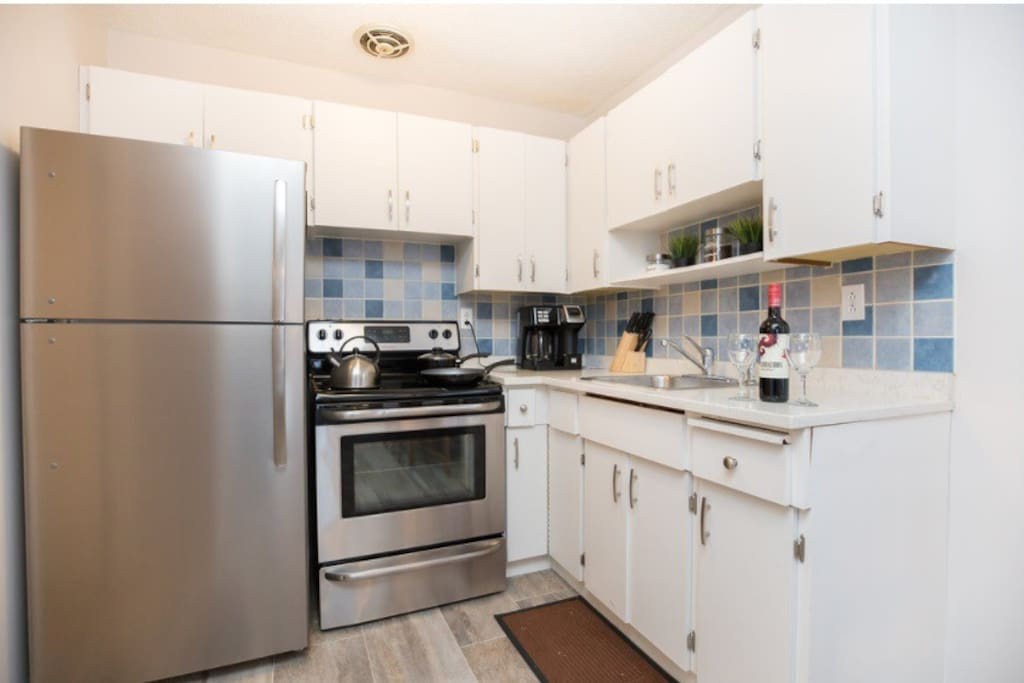 Bright kitchen with stainless steel appliances, granite counters and cooking utensils.