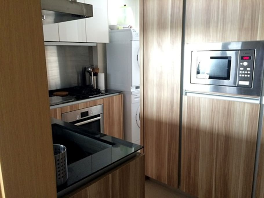 Kitchen with granite surfaces, microwave, sink, hobs and oven. Large fridge freezer is on the right out of shot.