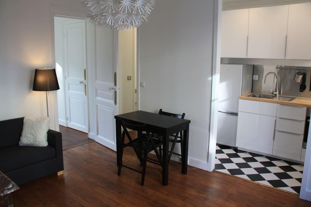 Salon avec canapé lit, table à manger extensible et ses 4 chaises. Cuisine équipée ouverte sur le salon.