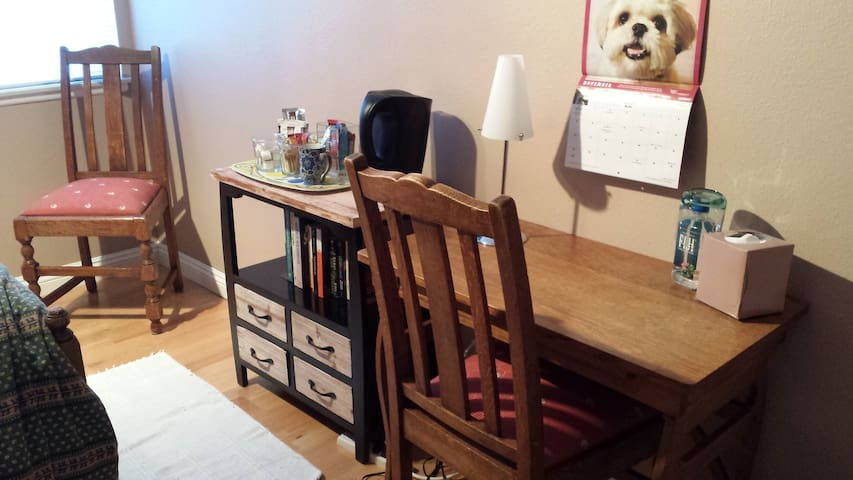 A writing desk where you can set up your laptop. The cabinet to the left equipped with electric kettle.