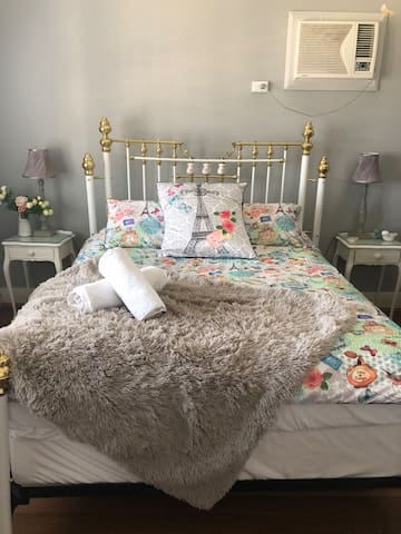 Main bedroom with queen size bed and air conditioning.