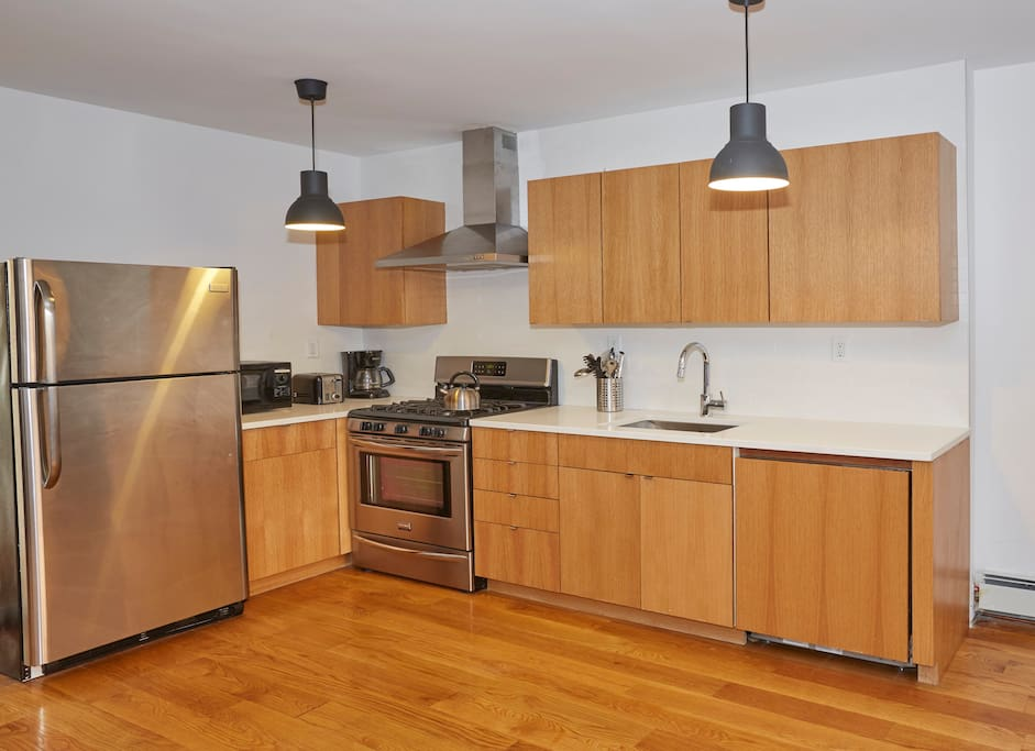 Modern, renovated kitchen ready for you to make some great meals. It has quartz countertops, full size, new stainless steel appliances including a dishwasher hidden behind the cabinetry.