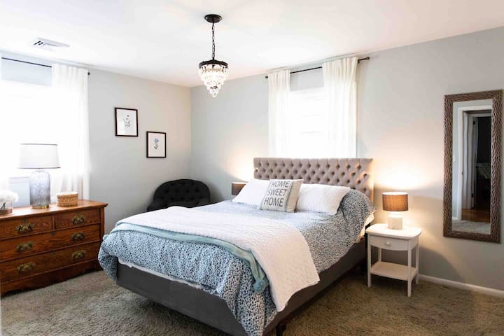Master bedroom suite with queen bed and attached private bathroom