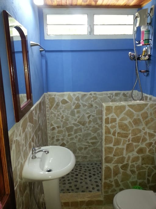 Bathroom with stone tiles and river rock shower floor.