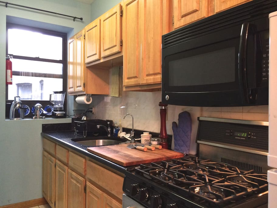 Sunny galley-style kitchen has a full-size gas stove & microwave, blender, coffee grinder, electric kettle, and is fully-stocked with gourmet cookware.