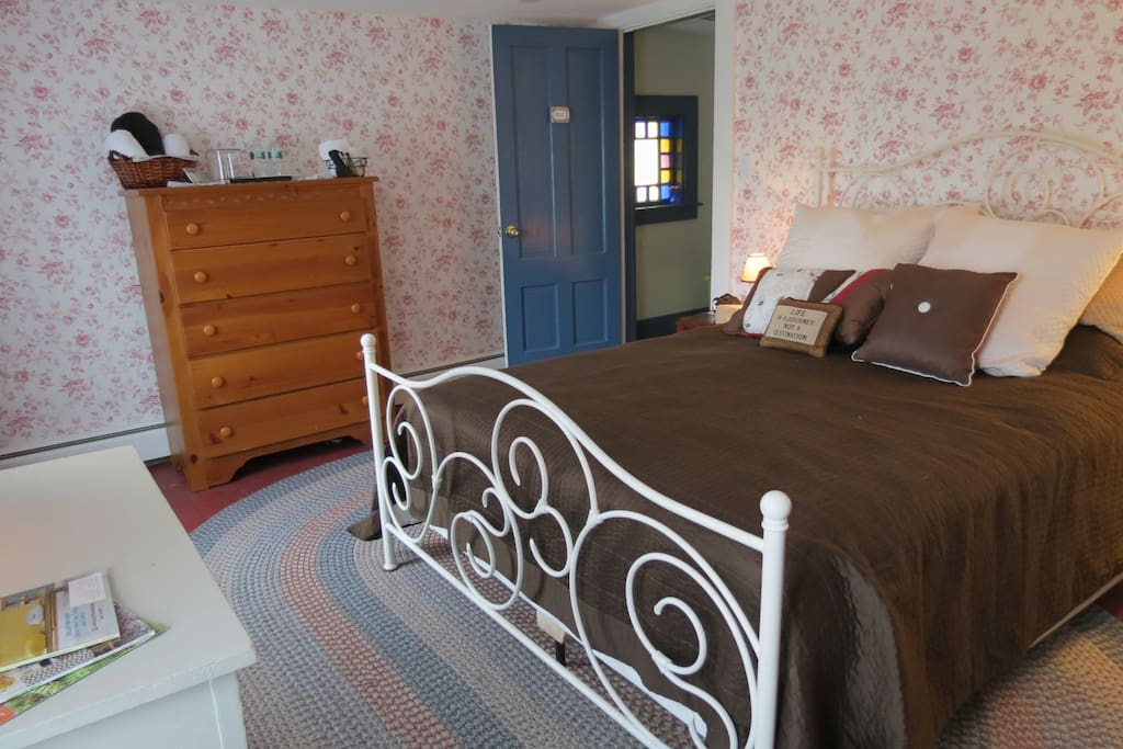 The Red Room has wood floors, queen bed, desk and extra seating.
