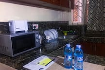 kitchen with a microwave,bread toaster,electric kettle,fridge and gas cooker,cups and plates plus general cutlery