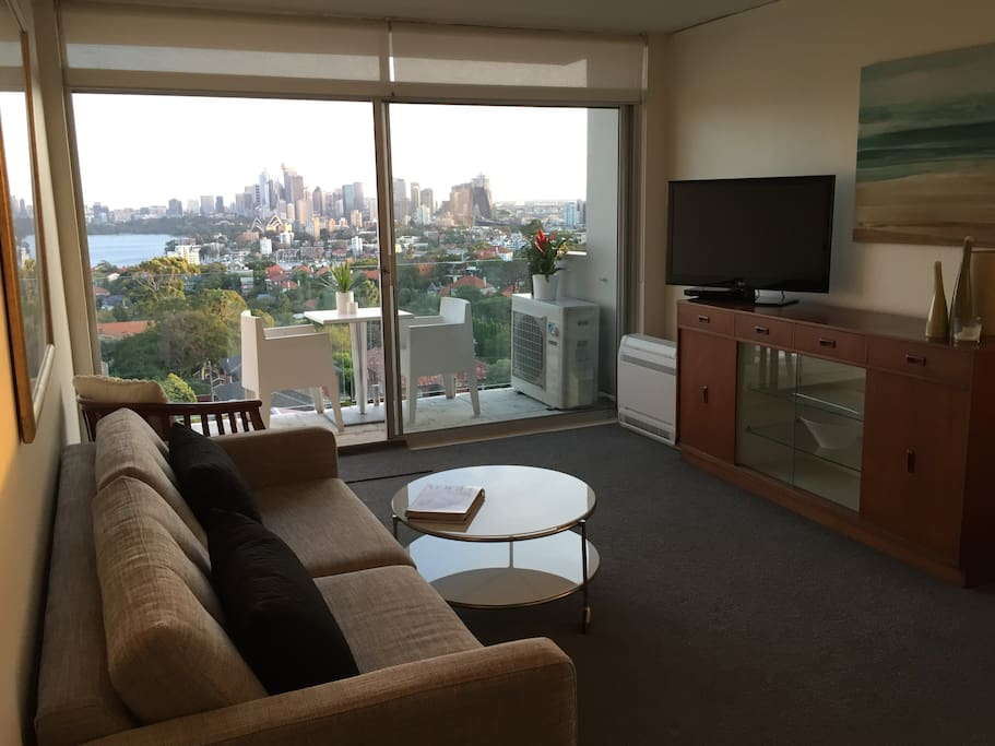 Lounge with TV and DVD opening onto balcony.  The lounge is a double sofa bed.  The air conditioning unit sits on the floor behind the TV. The view is beautiful.