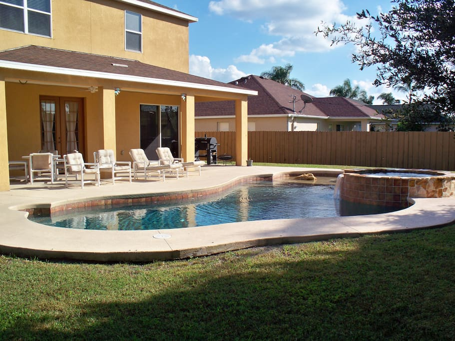 Fenced back yard with covered patio and pool with spa