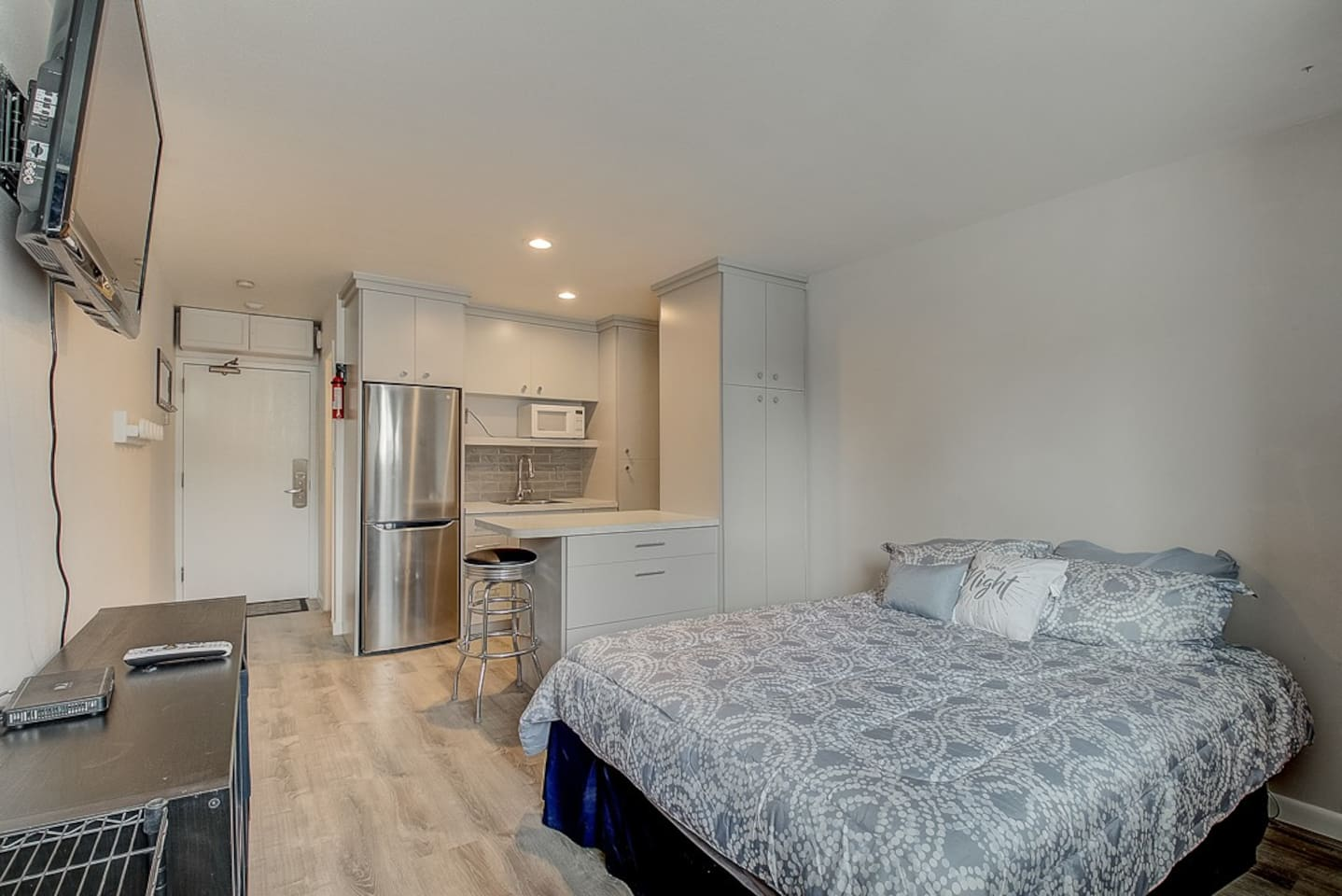 This photo shows a brand new Remote controlled adjustable queen size bed, kitchenette, workspace, flatscreen remote control television, stainless steel fridge and freezer as well.