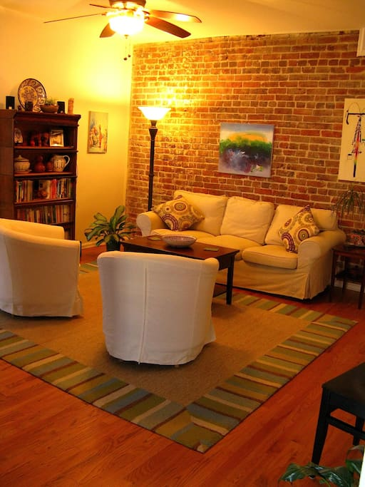 Warm living room with exposed brick wall.