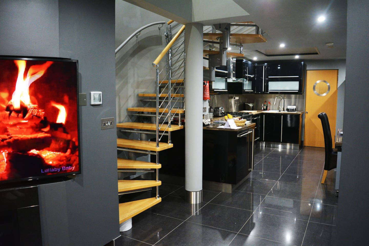 """An Open Plan Lounge With 60"""" Smart TV and Polished Porcelain Flooring Leading to a Spacious Black Gloss and Chrome Kitchen Area. *Highlight* Beech Tread, Chrome Rail Staircase Immersed In Urban Grey Decor"""