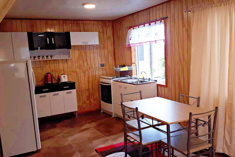 Cocina, posee agua caliente, cocina a gas, hervidor eléctrico, tostador de pan, muebles, mesa para 4 personas, refrigerador y menaje.