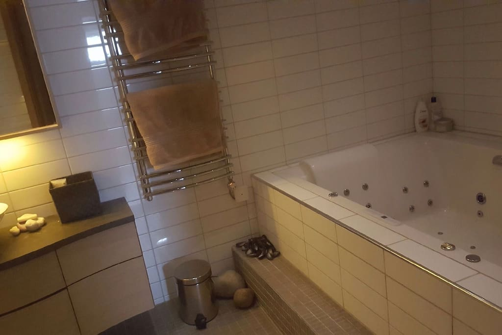 Badrum med handfat och jacuzzi. Bathroom with a sink and a jacuzzi.