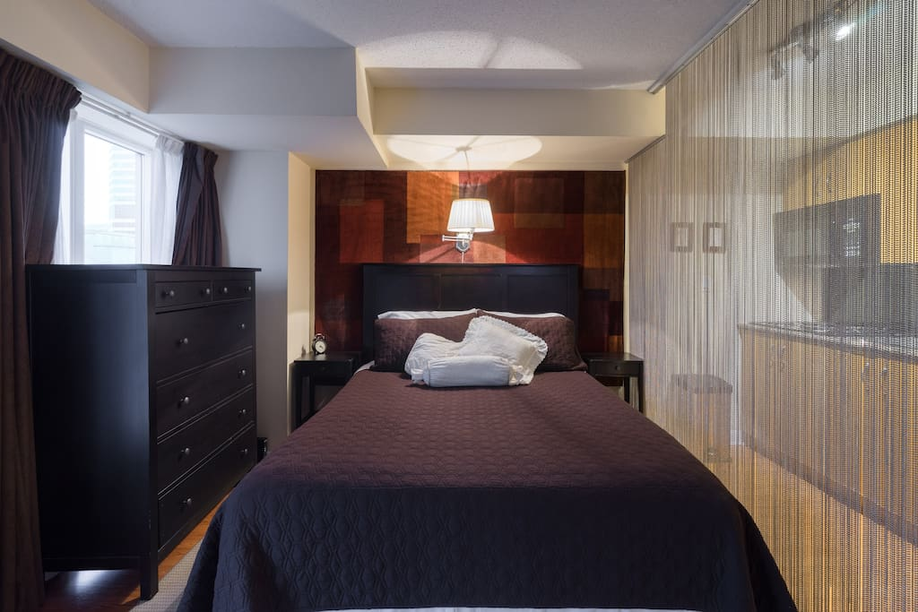 Comfortable Queen bed in this corner suite with many windows.  Blackout curtains throughout for those who are light sleepers.