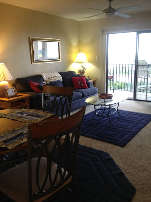 Comfortable living/ dining area with balcony overlooking ocean.