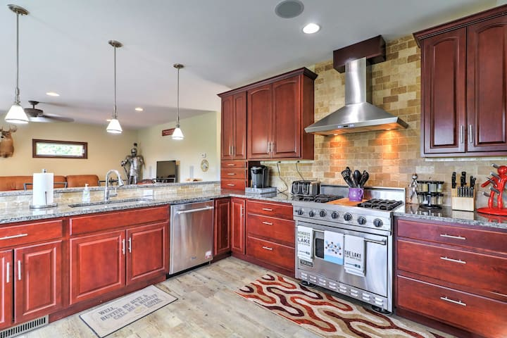 This fully equipped kitchen, complete with granite counters, red wood elements, and updated appliances, is truly a chef's dream come true.