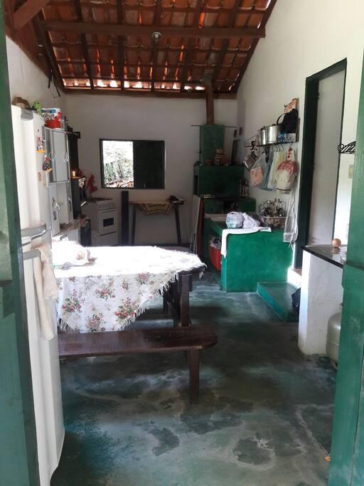 Cozinha equipada com fogão de lenha e gás, geladeira e utensílios em geral