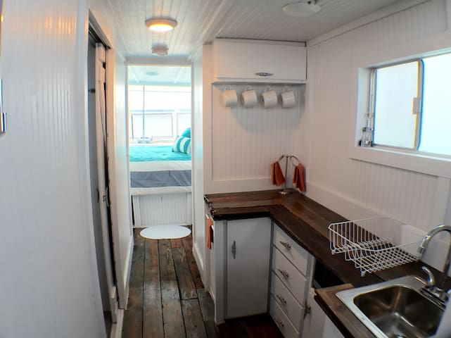 Galley (kitchen) with reclaimed hardwood counter tops, full sink, microwave, and everything you'd need to prepare a full meal.