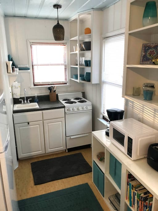 Full-service kitchen with fridge, dishes, pots & pans, coffee maker, toaster, and microwave.